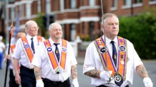 Four Orangemen marching. One of which proudly carries a ceremonial sword.