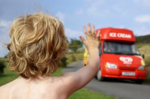A small child hails an ice cream van