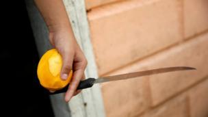 Juany Iznaga holds a mango and a knife as she eats the fruit at her house in La Fria, Venezuela.