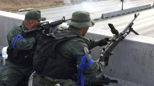 Militares con brazaletes azules apuntan sus armas