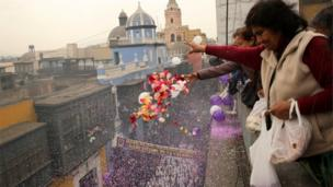 Women wave flowers and balloons from a balcony of a story building as the procession passes