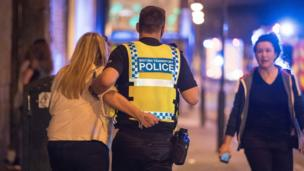 Police help the injured near the Manchester Arena after an explosion.