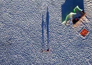 แสงอาทิตย์ที่คล้อยต่ำทำให้เกิดเงายาวทอดบนชายหาดที่เมืองแห่งหนึ่งในโปแลนด์