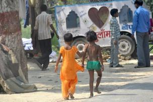 Two children hold hands as they walk along the street.