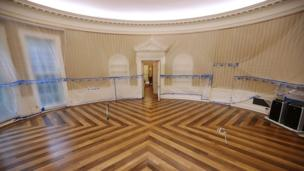 The Oval Office sits empty and the walls are covered with plastic sheeting during renovation work