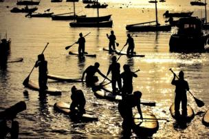 Paddle boarders sail as the sun sets and reflects on the water