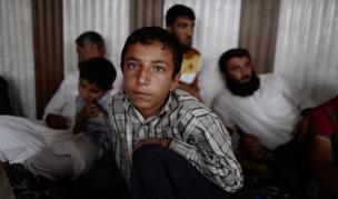 طفل يجلس مع أسرته في غرفة مكتظة بمدنيين في كوكجلي. وفي الوقت الذي كانت فيه قوات الأمن العراقية تنظم حملات في المدينة، كان مسلحو تنظيم الدولة الإسلامية يمنعون المدنيين من المغادرة ويطلقون النار على كل من يسعى لذلك