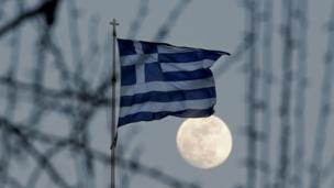 Bandera de Grecia frente a una gran Luna llena en Atenas