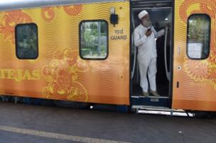In this photograph taken on May 21, 2017, an Indian guard communicates with the driver during a trial of the Tejas Express luxury train the Tejas Express luxury train before its first journey between Mumbai and Goa at the Chattrapati Shivaji Terminus terminus station in Mumbai.