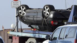 An upside-down car being driven on a transporter