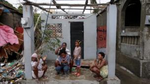 Family sit at entrance to damaged home in Les Cayes, Haiti, on 5 October 2016