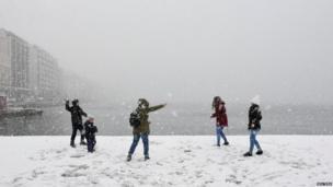ग्रीस के थैसोलिनिकी इलाके में एक दूसरे पर बर्फ़ के गोले बनाकर खेलते लोग.