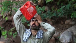 رجل يصب على نفسه مياه مسربة من أنبوب مكسور للتغلب على موجة الحر في إسلام آباد، باكستان