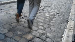 Legs of a couple walking on a cobble street