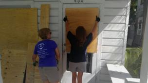 Women putting boards on front door in Key West, Florida