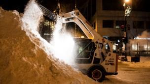 Un cargador frontal removiendo nieve en la calle