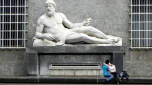 عاشقان تحت تمثال في مدينة تورينو الإيطالية