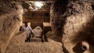 أثري مصري يفحص غرفة دفن تم العثور عليها في الكشف الأثري