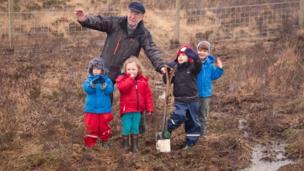 Man and children cut turf on Skye