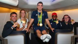 Pete Reed, Helen Glover, Max Whitlock, Nicola Adams and Katie Archibald pose for a picture on the flight home