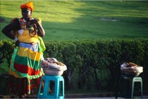 Palenquera con un delantal bastante colorido vende panelitas de coco.