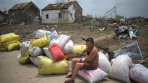 """A woman sits with her belongings in front of the rubble of her destroyed houses after a tornado in Funing, in Yancheng, in China""""s Jiangsu province on June 24, 2016."""