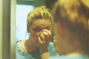 A woman does her mascara in the mirror