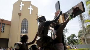"""A man dressed up as a Roman soldier hangs a sign on a cross during a re-enactment of the crucifixion of Jesus Christ on Good Friday along a road near St. Leo""""s Catholic church in Lagos"""
