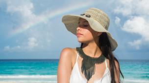 Mujer joven en la playa y un arcoíris al fondo