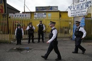 Police officers stand on duty in Barking, east London on following a dawn raid on a property,