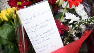 """A bunch of flowers with a written messages which says: """"Thank you for all your hard work. Our thoughts are with your family and colleagues. You will be remembered for your tireless work for the less fortunate. Rest in peace. An inspirational lady."""""""