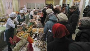 People queue for food at a polling station in Kazan, Russia, on 18 March 2018