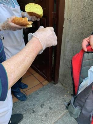 Unas manos con un trozo de pan y una mochila abierta