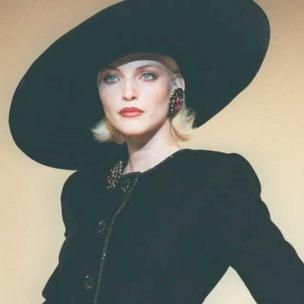 A model in large black hat, tilted to side and velvet black dress in July 1995