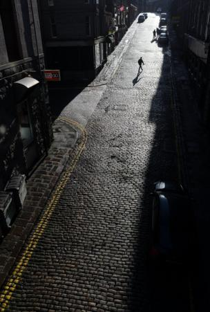 An aerial view of a street with a lone man and his shadow