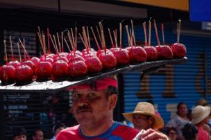 Man balancing tray of apples on his head