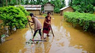 यह तस्वीर भारत के उत्तर-पूर्वी राज्य असम की है, जहां एक बाढ़ प्रभावित गांव में दो युवतियां पानी में डूब चुके अपने घर तक पहुंचने की कोशिश कर रही हैं.