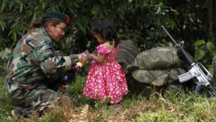 A Farc rebel pours juice for a local girl as she arrives at a transition zone in Cauca province in Colombia on 31 January 2017