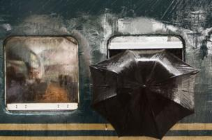 "At Tongi railway station in Gazipur, Bangladesh, a man looks out of a rain-sodden train towards Moin Ahmed's camera. ""Suddenly I found a pair of curious eyes were looking at me through the window,"" he said, ""and on his left an umbrella provided protection from the rain."