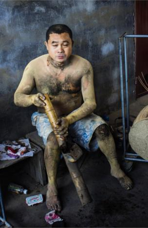 An incense worker sitting down on his break