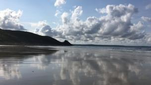 Clouds mirrored on Newgale beach in Pembrokeshire by Sue Pasternak