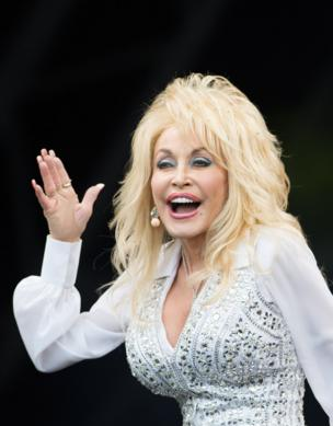 Dolly Parton holds her hand up to the audience