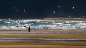 A lone walker looks on at the kite surfers on Oxwich Bay, Gower, taken by John Minopoli