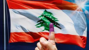 شخص يرفع إصبعه المغمور بالحبر الفسفوري أمام على لبنان