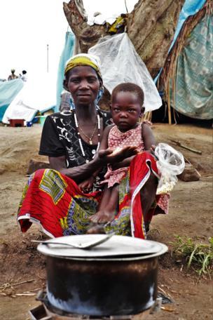 Une mère avec son fils dans les bras qui fait la cuisson.