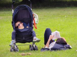 Un niño duerme en un cochecito mientras su madre lee sobre el césped en un parque.