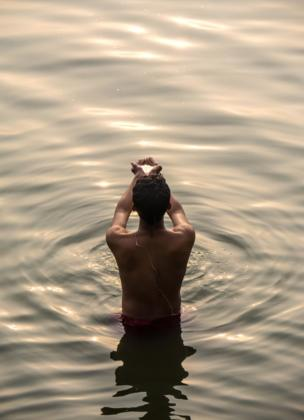 A man taking a ritual bath in the Ganges during a winter sunrise shows his faith. He braves the cold and polluted water with faith that the sacred river is pure and has the ability to purify those that bathe in it.