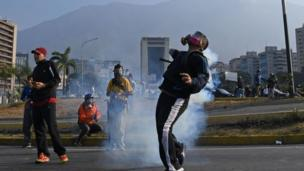Un manifestante intenta lanzar una lata de gas lacrimógeno