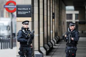 Armed police officers patrol outside Westminster underground station