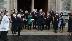 Mourners and politicians clapped as the funeral cortege left the cathedral.